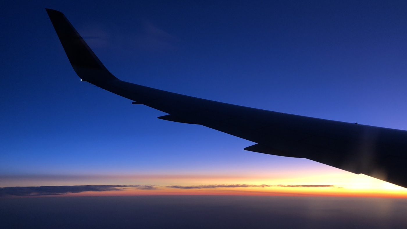 view of a sunrise outside of an airplane window, with a airplane wing spread across the frame